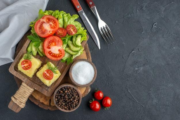 Vista frontale ravvicinata del formaggio di verdure fresche tritate e intere su tagliere e spezie sul lato destro su superficie nera