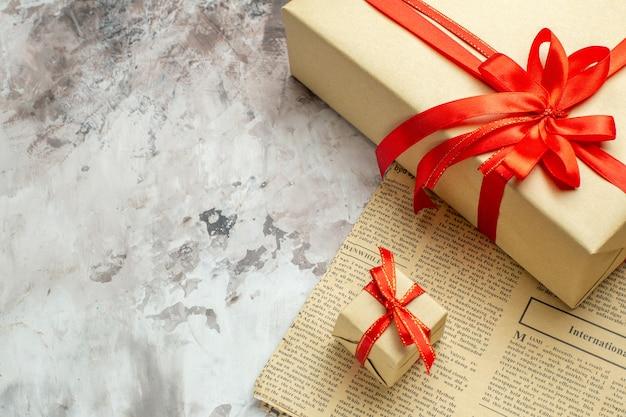 Vista frontale ravvicinata regali di natale con fiocchi rossi su sfondo bianco