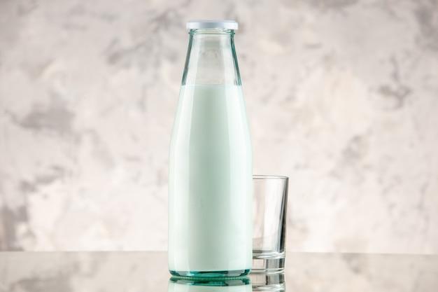 Vista frontale ravvicinata chiusa e riempita con bottiglia di vetro per il latte e tazza su sfondo bianco di fumo con spazio libero