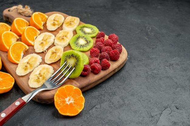 Vista frontale ravvicinata della raccolta di frutta fresca tritata su un tagliere di legno in vista orizzontale