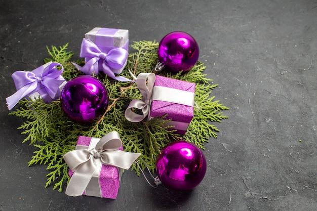 Vista frontale ravvicinata di regali colorati e accessori decorativi su sfondo scuro