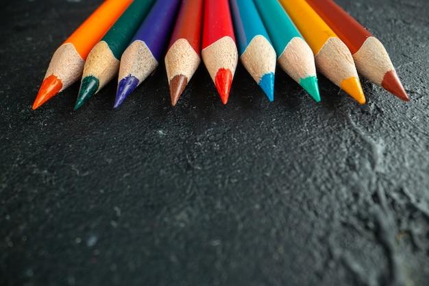 Vista frontale ravvicinata matite colorate allineate su disegno scuro scuola di arte fotografica a colori