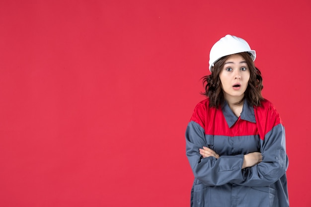 Front close view of confused female builder in uniform with hard hat crossing her arms on isolated red wall
