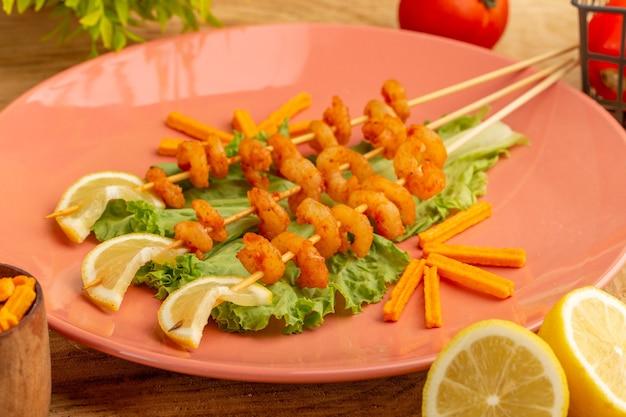 Вид спереди крупным планом приготовленные креветки на палочках внутри персиковой тарелки с ломтиками лимона масло зеленого салата