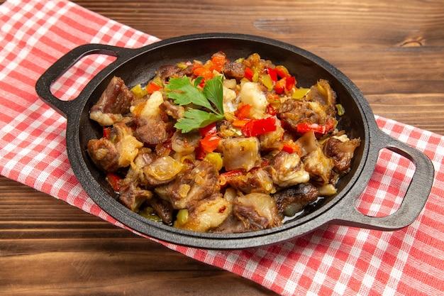 Farina di verdure cotte vista frontale ravvicinata comprese verdure e carne all'interno sullo scrittorio di legno marrone