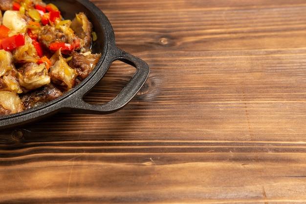 木製の茶色の机の上に肉と野菜の食事を正面から見る