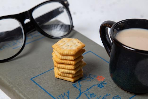Una vista frontale vicino tazza di latte con occhiali da sole e latte sulla superficie della luce