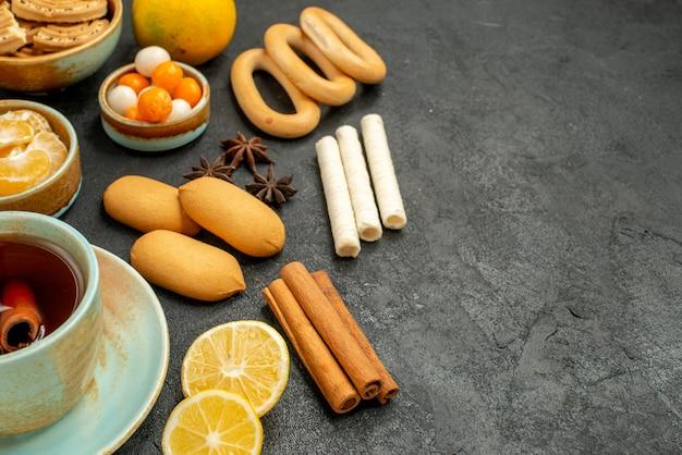 Вид спереди крупным планом чашка чая с конфетами, печеньем и фруктами на сером столе, чай, сладкое печенье