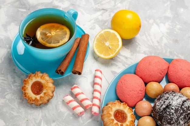 フレンチマカロンクッキーとライトホワイトの壁にケーキシュガービスケット甘いケーキキャンディークッキーとお茶の正面のクローズビューカップ