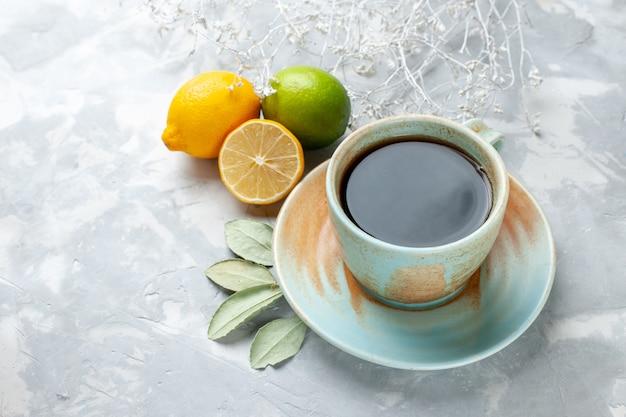 白い机の上に新鮮なレモンとお茶の正面のクローズビューカップフルーツ新鮮な柑橘類のエキゾチック