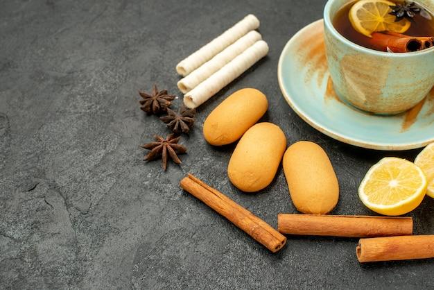 灰色のテーブルビスケットの甘いクッキーにレモンとクッキーとお茶の正面のクローズビューカップ