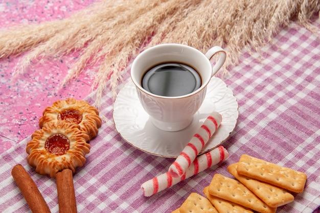 Vista ravvicinata anteriore tazza di tè con biscotti alla cannella e cracker in forno dolce rosa chiaro scrivania zucchero biscotto