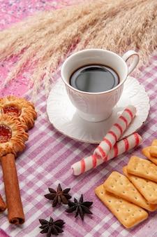 Vista ravvicinata anteriore tazza di tè con biscotti alla cannella e cracker su rosa scrivania biscotto zucchero dolce cuocere