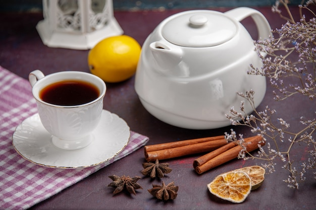 Front close view cup of tea with cinnamon and kettle on dark surface tea drink lemon color