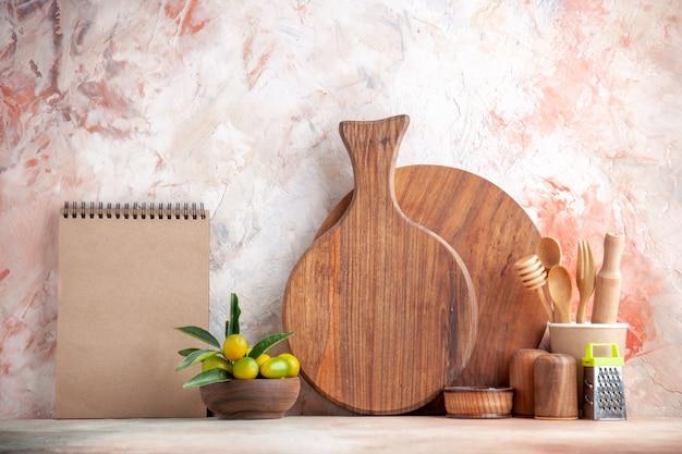 Vista frontale ravvicinata del tagliere cucchiai di legno grattugia kumquat in vaso e quaderno su superficie colorata colorful