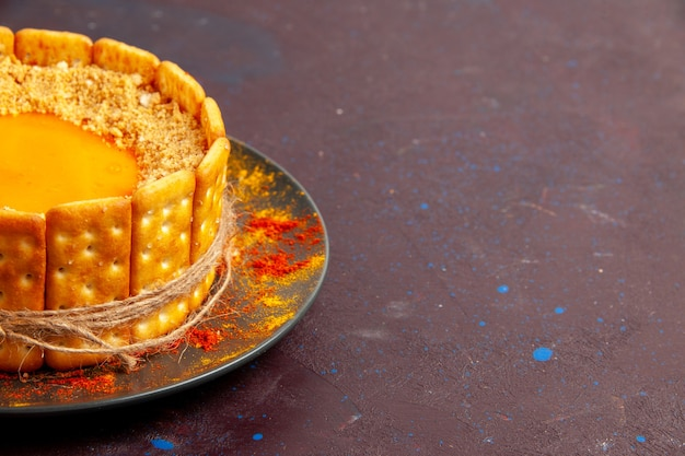 Vista ravvicinata anteriore deliziosa torta luminosa con crema e biscotti cracker sui biscotti dolci di zucchero torta biscotto scuro scrivania torta