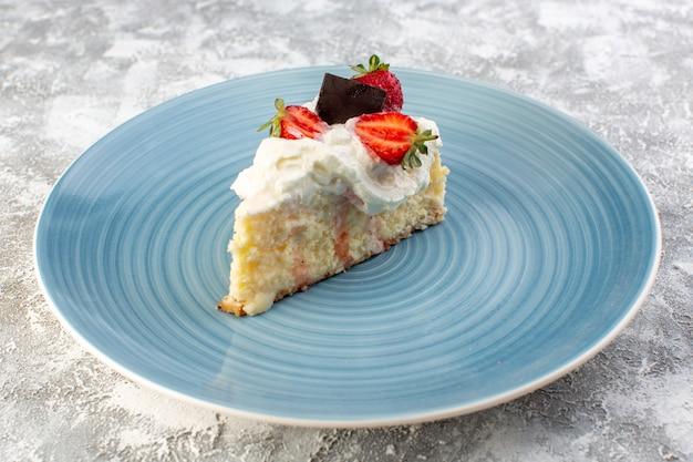 회색 표면에 크림과 딸기 블루 라운드 접시 안에 전면보기보기 맛있는 케이크 조각
