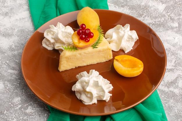 明るい机の上にクリームが入った茶色のプレートの中にアプリコットが付いた正面のおいしいケーキのスライス