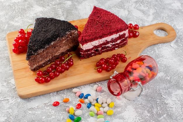 Фронт закрыть вид вкусные кусочки торта со сливочным шоколадом и фруктами на деревянный стол с конфетами
