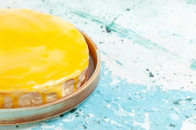 Torta deliziosa vista ravvicinata frontale con sciroppo giallo su superficie azzurra