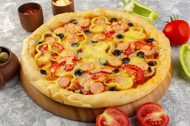 灰色の表面にオリーブ、ソーセージ、トマトのおいしい安っぽいピザの正面を閉じる