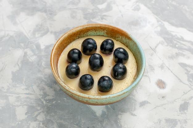 白い表面の小さな鍋の中にブドウが上にある正面のクローズビューおいしいクリームデザート