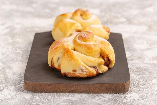 Vista ravvicinata frontale deliziosi pasticcini fruttati dolci al forno sulla superficie grigia torta pasticceria dolce infornare il tè