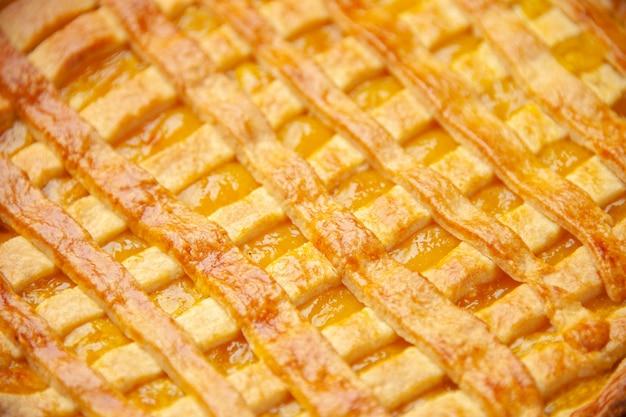 Спереди крупным планом вкусный желейный пирог на темно-синей поверхности печь тесто бисквитный торт сахарная выпечка десерт чай сладкий цвет