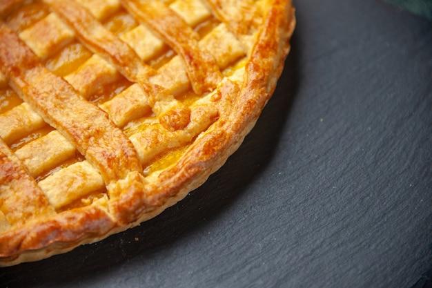 Спереди крупным планом вкусный желейный пирог на темной поверхности печь тесто бисквитный торт сахарная выпечка десерт чай сладкий цвет