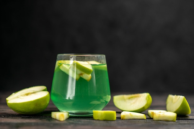 Front close view of delicious juice in a glass and an chopped apple on dark background