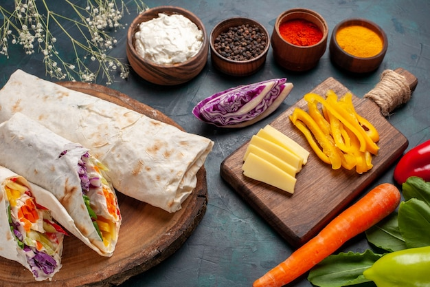 正面を見るおいしい肉のサンドイッチ青い机の上に調味料を入れて串焼きにした肉のサンドイッチ