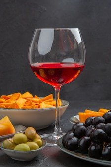 Front close view of delicious red wine in a glass goblet and various snacks on a black background