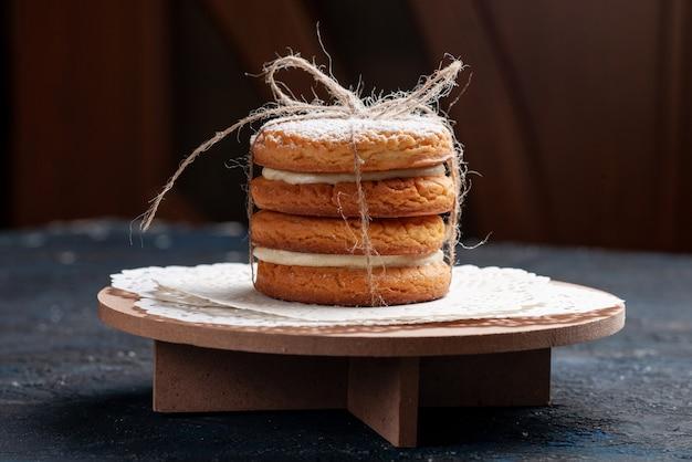 正面を見るとおいしいサンドイッチクッキーが濃い青のデスクケーキに美味しく結ばれました