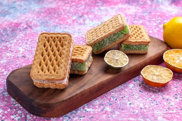 핑크 책상에 레몬 전면 닫기보기 맛있는 샌드위치 쿠키.