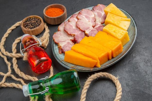 Vista frontale ravvicinata di deliziosi snack bottiglie cadute peperoni su asciugamano e corda su sfondo nero