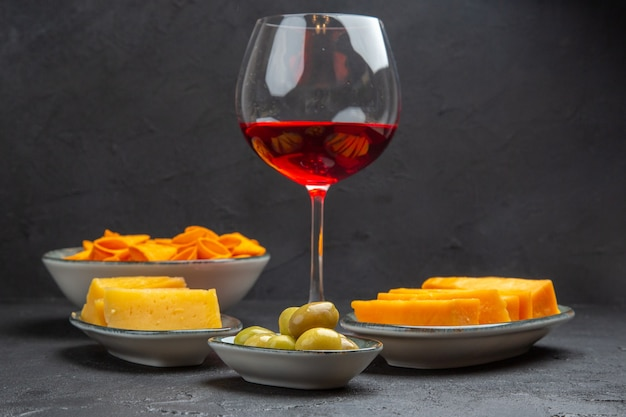 Front close view of delicious snacks for wine in a glass goblet on a black background