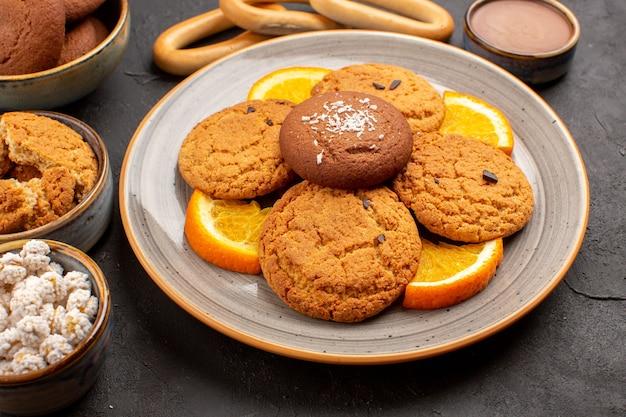 Biscotti di zucchero deliziosi vista frontale ravvicinata con arance fresche a fette su oscurità