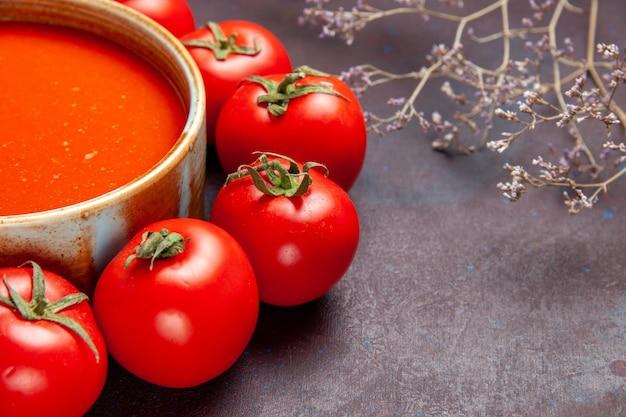 Vista frontale ravvicinata deliziosa zuppa di pomodoro circondata da pomodori rossi freschi su spazio scuro