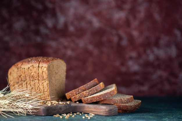Front close view of dietary black bread spikes wheats on wooden cutting board on blue maroon mixed colors background