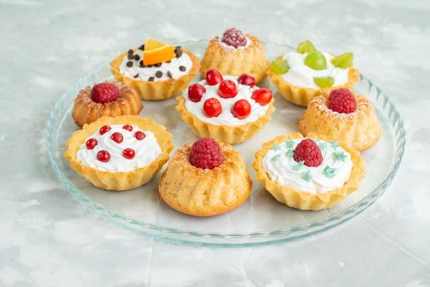 Vista ravvicinata anteriore diverse torte con panna e frutta fresca sulla superficie chiara zucchero biscotto dolce