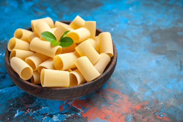 Front close view of dinner preparation with pasta noodles with green in a brown pot on blue background
