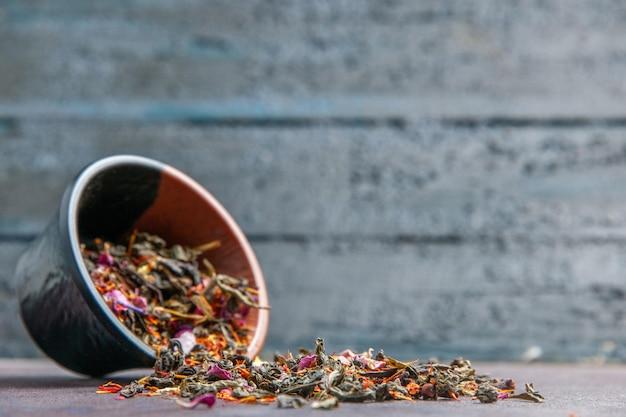 Front close view dried fresh tea on dark background plant tea dust flower flavor