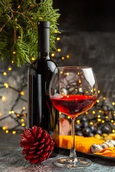 Vista frontale ravvicinata del vino rosso secco in un bicchiere e in una bottiglia accanto a snack e cono di conifere su sfondo grigio