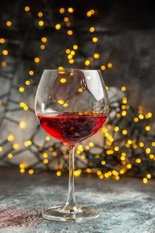 Vista frontale ravvicinata del vino rosso secco in un bicchiere su sfondo grigio