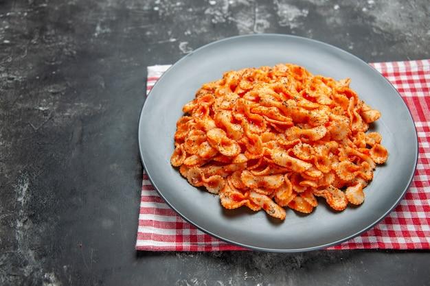 Vista frontale ravvicinata di un facile pasto di pasta per cena su un piatto nero su un asciugamano spogliato rosso