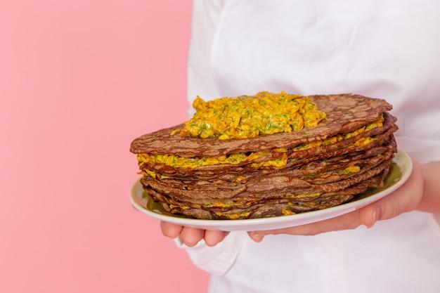 Pasticcere femminile di vista ravvicinata anteriore in usura bianca che tiene i pasticcini deliziosi sulla pasticceria dolce della pasticceria della parete rosa