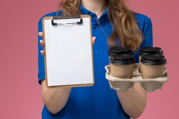 Corriere femminile vista ravvicinata anteriore in uniforme blu che tiene il blocco note e le tazze di caffè di consegna sul lavoro dell'azienda dell'uniforme di servizio leggero dello scrittorio