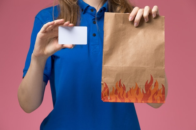 Front close view female courier in blue uniform holding white card and food package on pink light desk service uniform company job