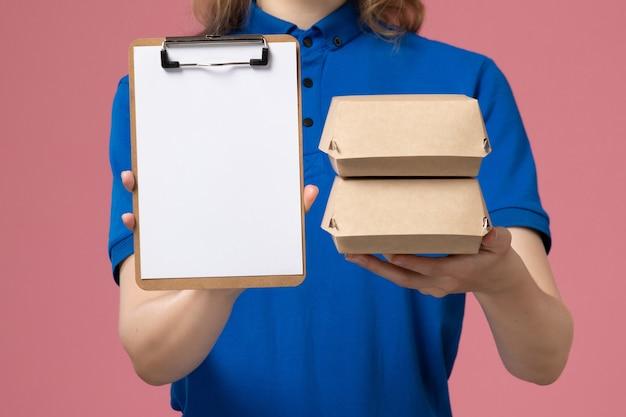 ピンクのデスク配達サービスの仕事の従業員に小さな配達食品パッケージとメモ帳を保持している青い制服の岬の正面のクローズビュー女性宅配便