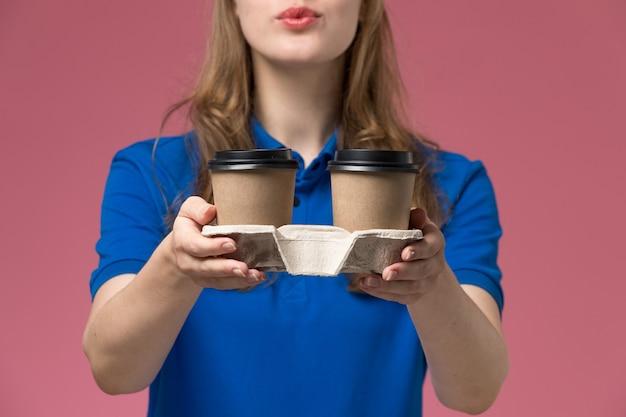 ピンクのデスクサービスの制服で茶色のコーヒーカップを配達する青い制服を着た正面の女性の宅配便会社の仕事を届ける